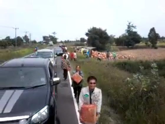 事故で散乱したビール箱を持ち去るタイ人たち