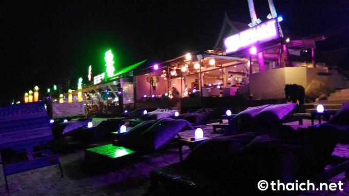 夜のビーチにはライトアップされたバーが並ぶ